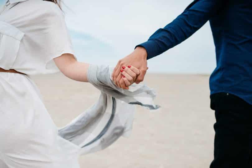 Homem e mulher correndo na praia de mãos dadas