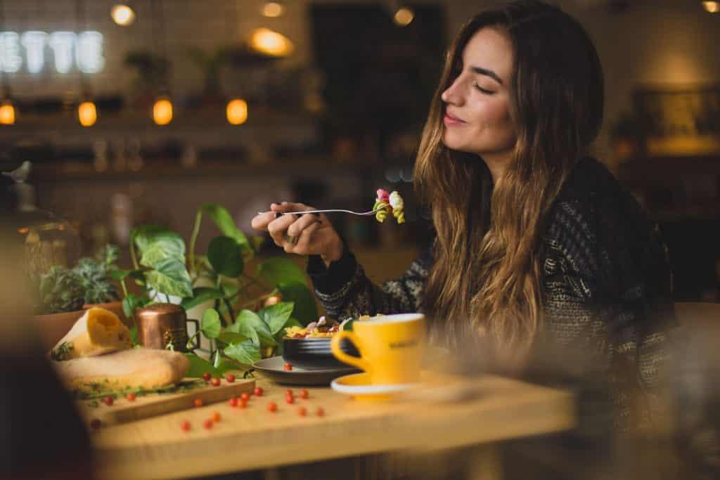 Mulher comendo macarrão colorido em uma mesinha de madeira.