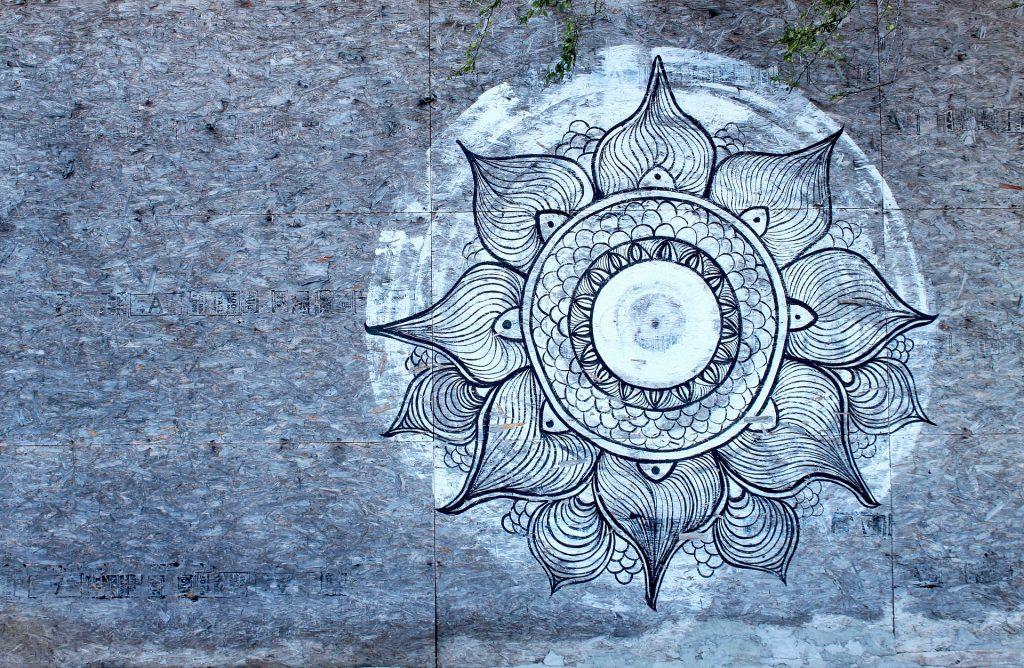 Linda imagem de uma manda lunar grafitada ao fundo de uma parede cinza.