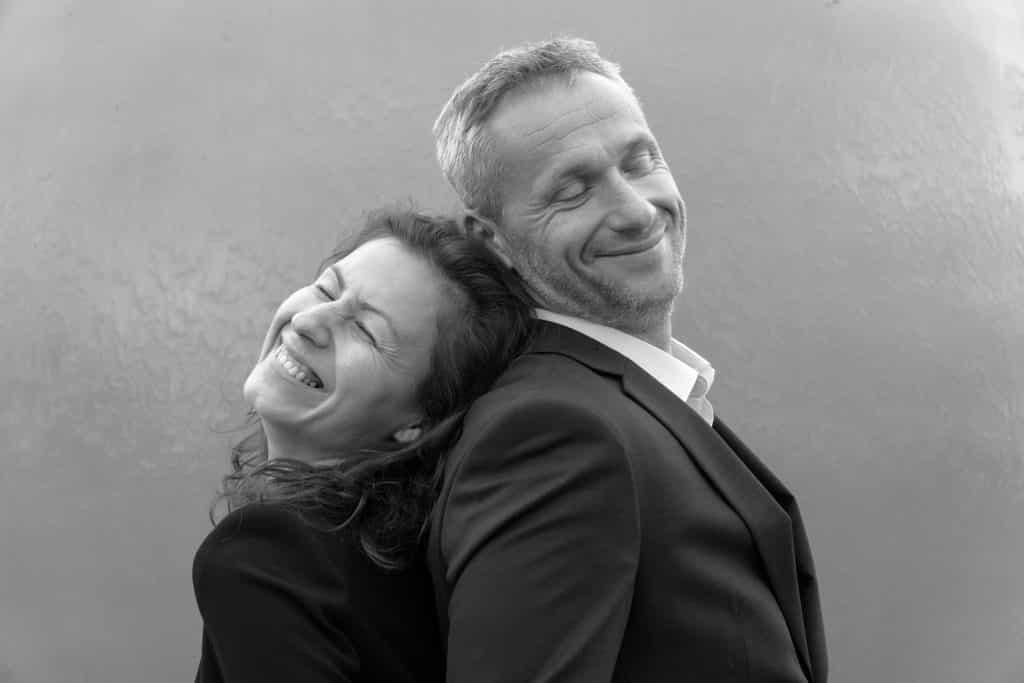 Imagem em preto e branco de um casal homem e mulher de meia idade. Eles estão de costas um para outro e estão felizes.