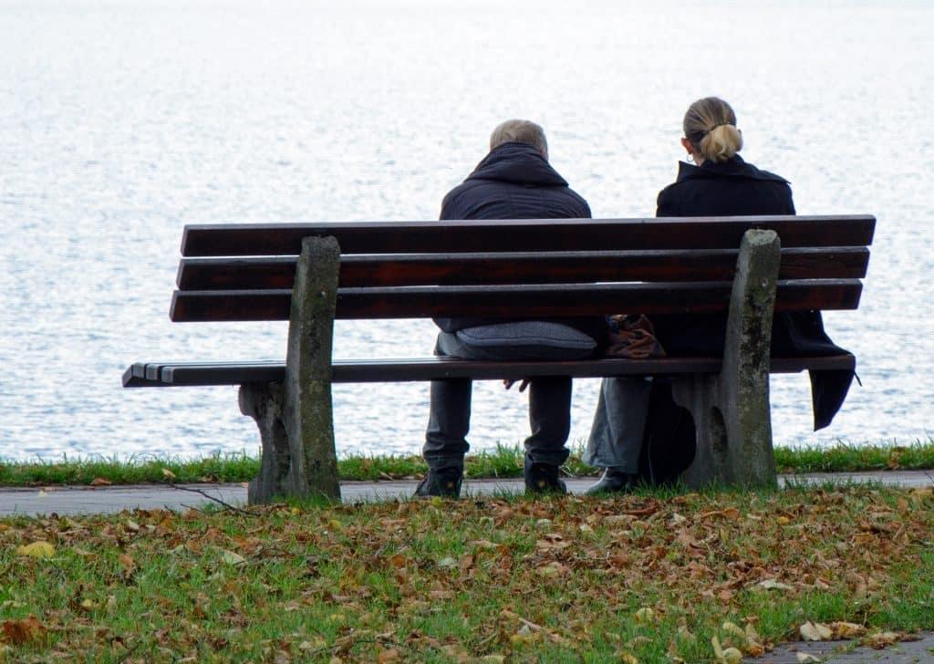 Imagem de um casal sentando em um banco de mandeira em frente a um lago. Ambos vestem casacos de inverno na cor azul.