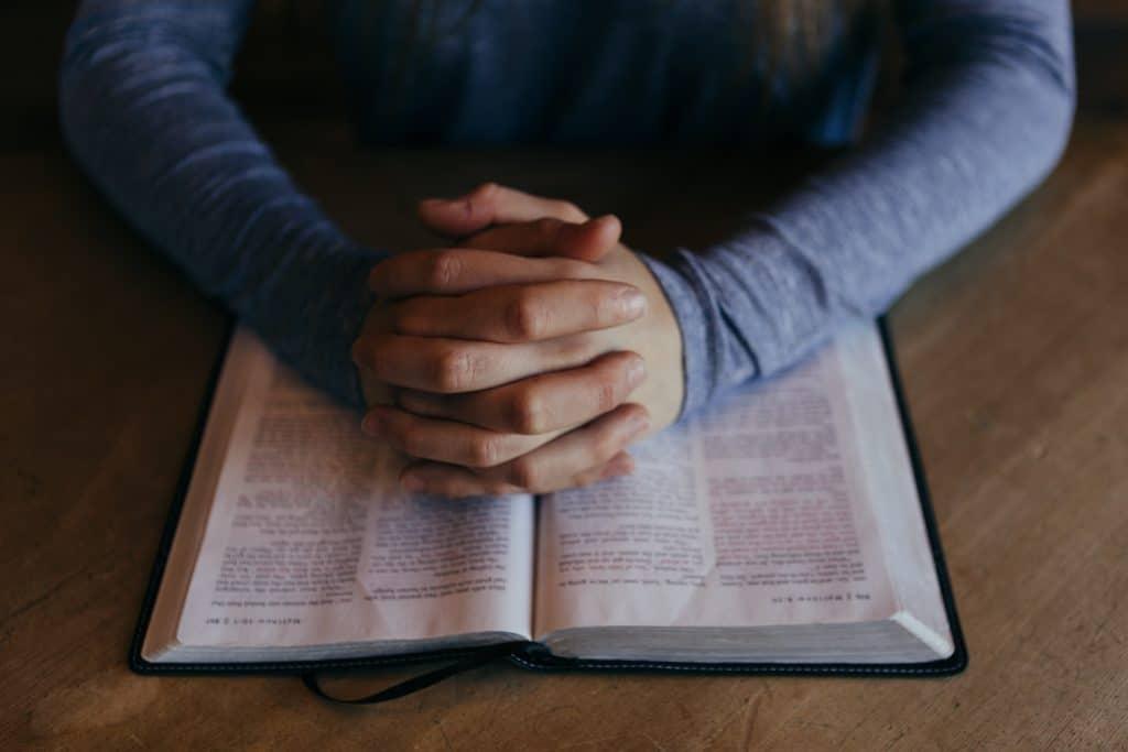 Pessoa orando com as mãos unidas em cima da bíblia aberta