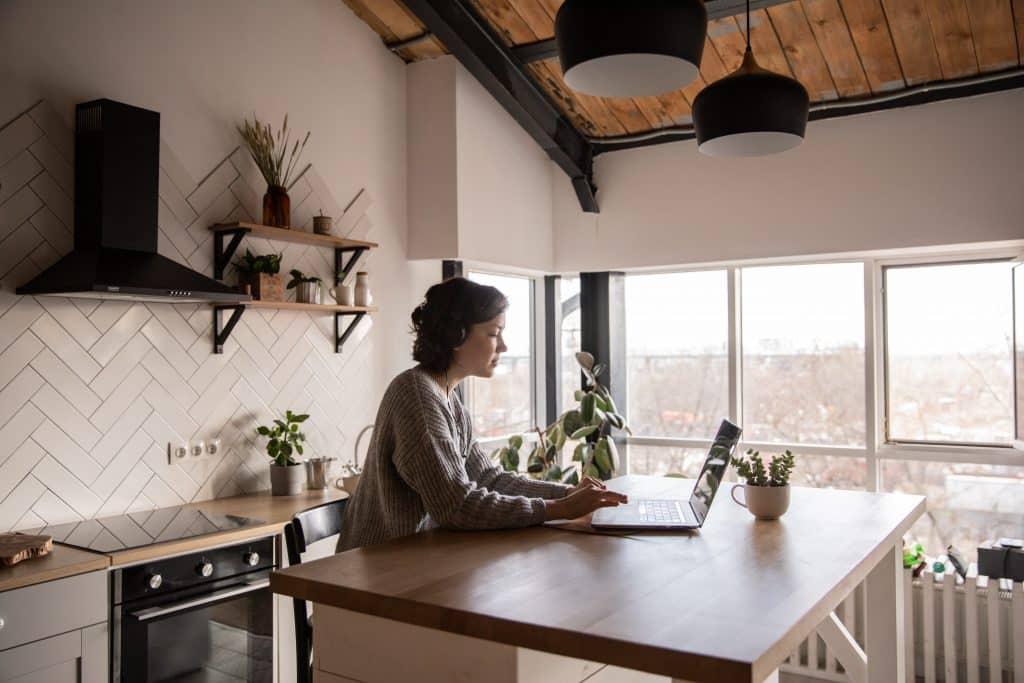 Mulher sentada na mesa da cozinha, usando seu laptop.