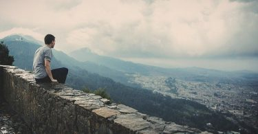 Homem sentado em muro baixo no topo de uma montanha, com vista para uma cidade.