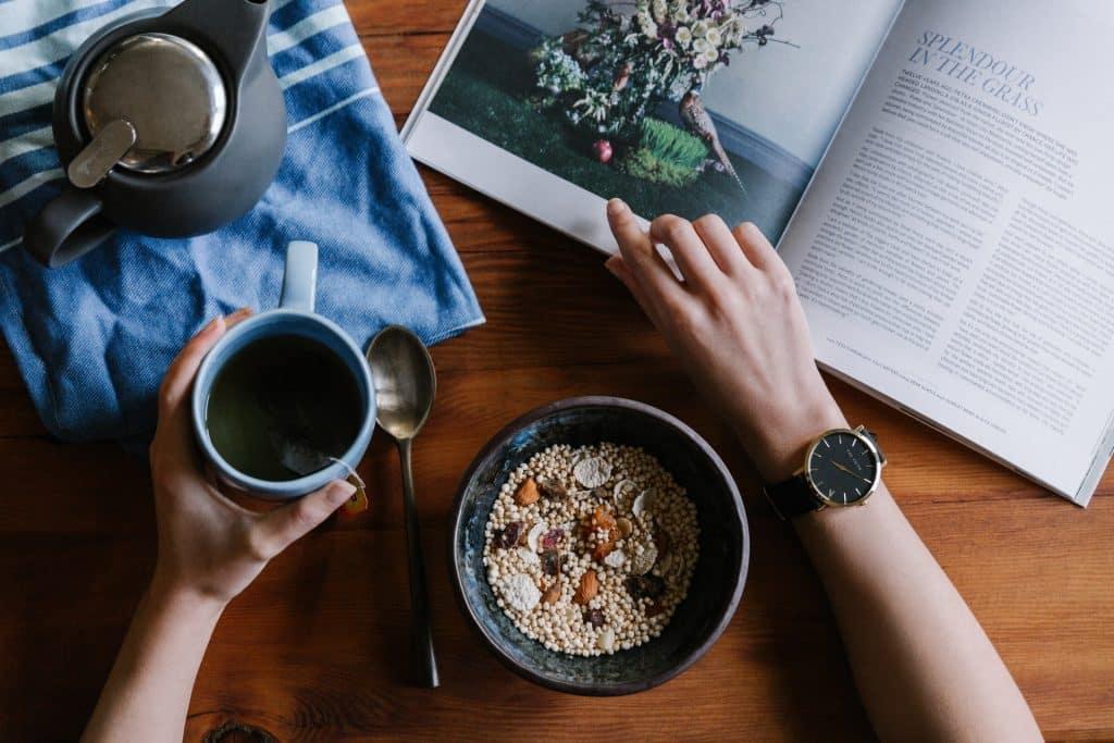 Pessoa segurando caneca com chá e folheando revista. Em sua frente, está uma tigela com cereais.