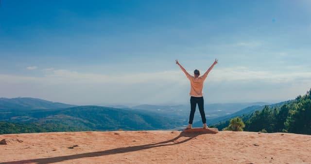Pessoa de braços abertos para o alto, no topo de uma montanha.