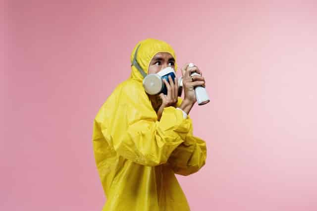 Homem vestido com roupa especial anti-contaminação com máscara e spray na mão