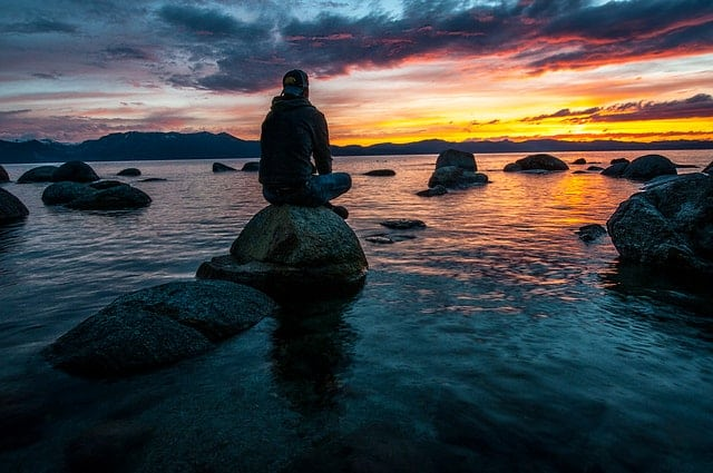 Pessoa sentada em pedra no mar, olhando para o pôr do sol.