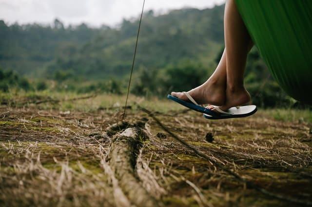 Pés de chinelos de alguém sentado em rede com chão de mato e paisagem verde