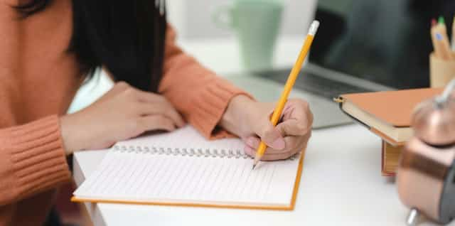 Pessoa escrevendo com lápis em caderno.