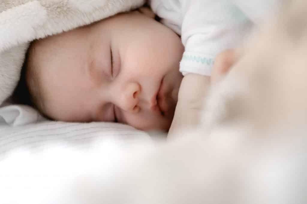 Bebê dormindo enrolado em uma cobertinha clara.