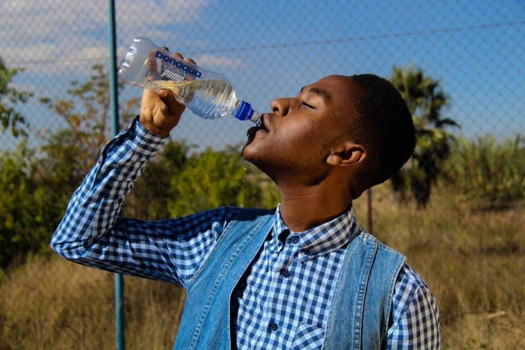 Recorte de um homem negro bebendo água de uma garrafa.