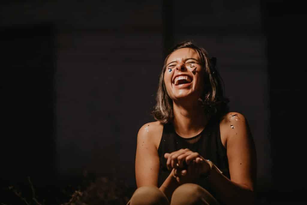 Mulher jovem gargalhando com os olhos fechados. Seu rosto e seus ombros estão com papéis brilhantes colados.