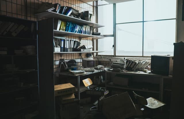 Sala de arquivos bagunçados com coisas quebradas e janela fechada