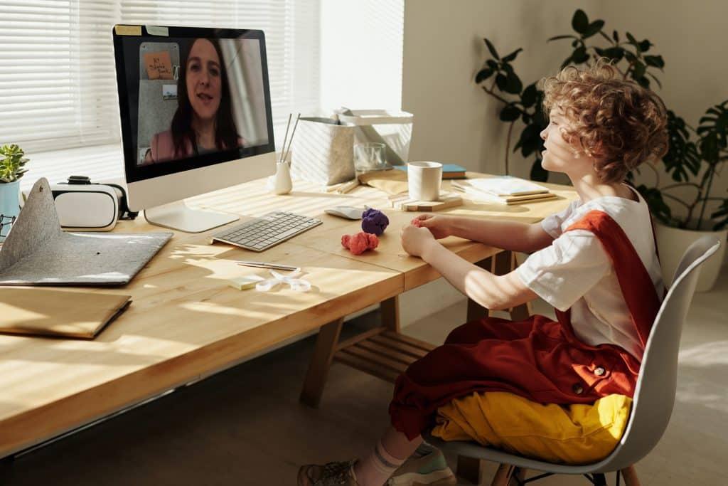 Criança sentada em frente a um computador, assistindo a uma aula por videochamada.