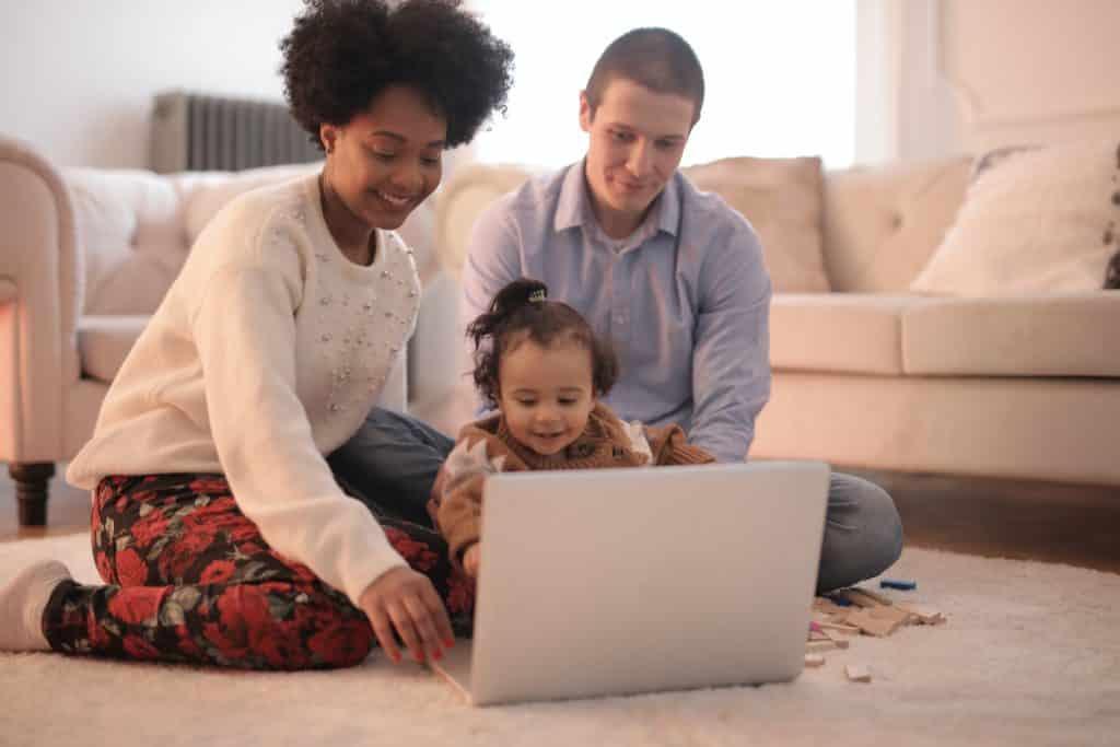 Homem, mulher e uma criança pequena sentados no chão da sala de estar, usando o computador.