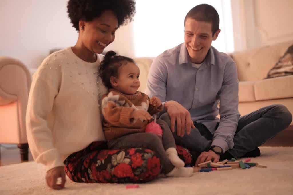 Homem e mulher sentados no chão, sorrindo. No colo da mulher, uma bebê também sorri.