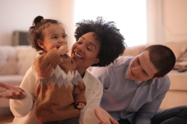 Família em sala de casa brincando sendo bebê, mãe e pai