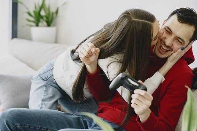 Garota dando beijo no rosto de garoto sorrindo com controle de vídeo game na mão