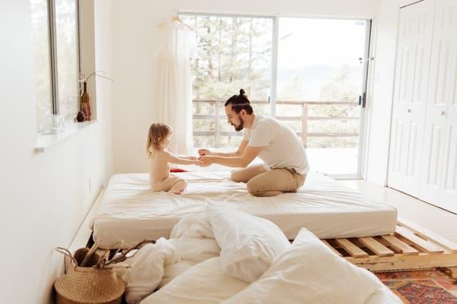 Pai e filha brincando na cama