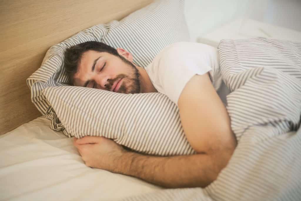 Homem deitado da cama, dormindo.