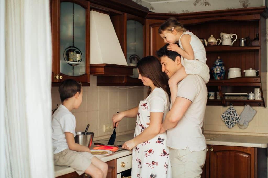 Família em cozinha. Um menino está sentado em uma bancada, uma mulher usa uma espátula dentro de uma frigideira e um homem segura uma menina pequena em seus ombros.