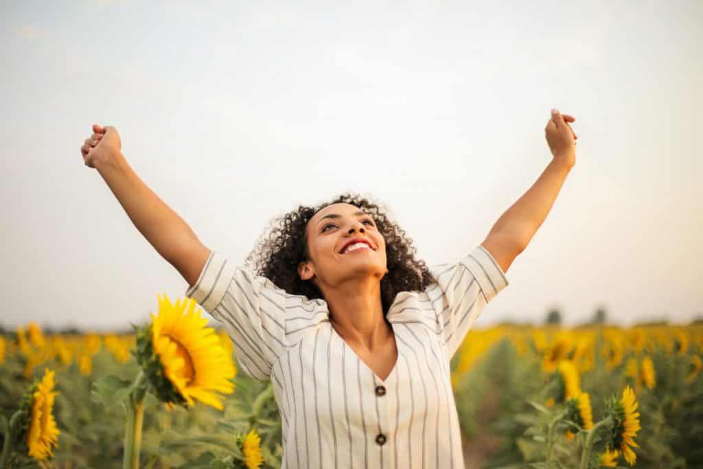 Mulher com os braços abertos, sorrindo e olhando para cima, em um campo de girassóis.