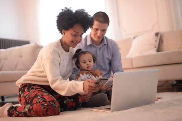 Pais e filha com celular e notebook no chão da sala