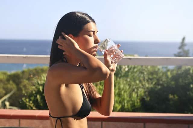 Mulher de biquíni bebendo água de perfil