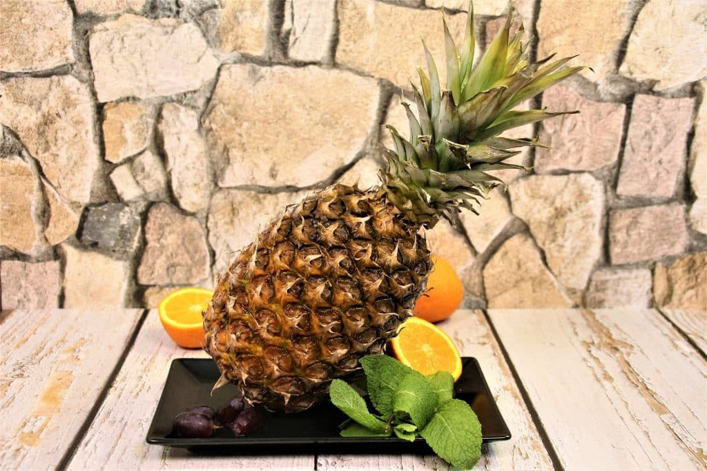 Imagem de um abacaxi. Ele está inteiro e sobre uma travessa de porcelana na cor preta, decorada com laranjas cortadas ao meio de folhas de hortelã.