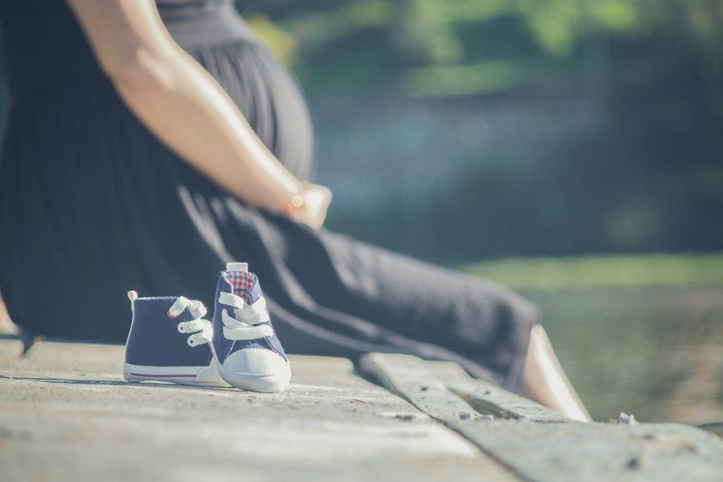 Imagem de uma mulher grávida. Ela veste um vestido preto e segura com suas mãos a barriga. Ela está sentada em um banco de concreto. Ao lado, um tênis azul de récem nascido.