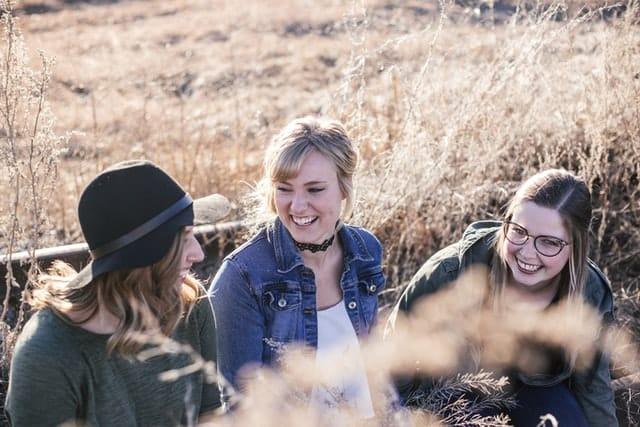 Amigas conversando em banco sorrindo