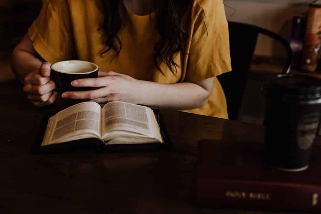 Mulher tomando xícara de café com um livro aberto em seu colo