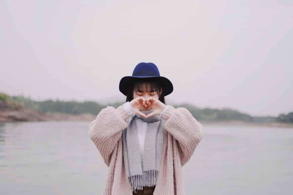 Menina fazendo um coração com as mãos. Ela está usando um casaco cor-de-rosa e um chapéu azul escuro. Ao fundo há um lago.