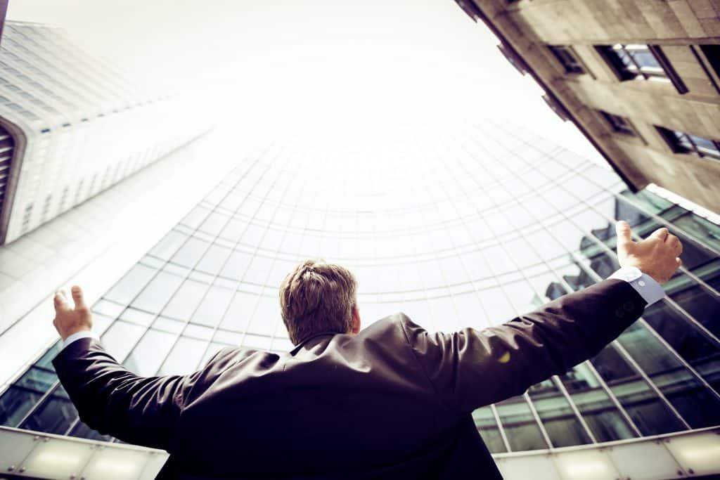 Homem de roupas sociais olhando para cima com os braços abertos.