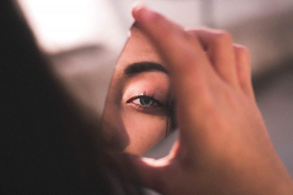 Foto de uma mulher segurando um espelho quebrado, que reflete a figura de seu olho.