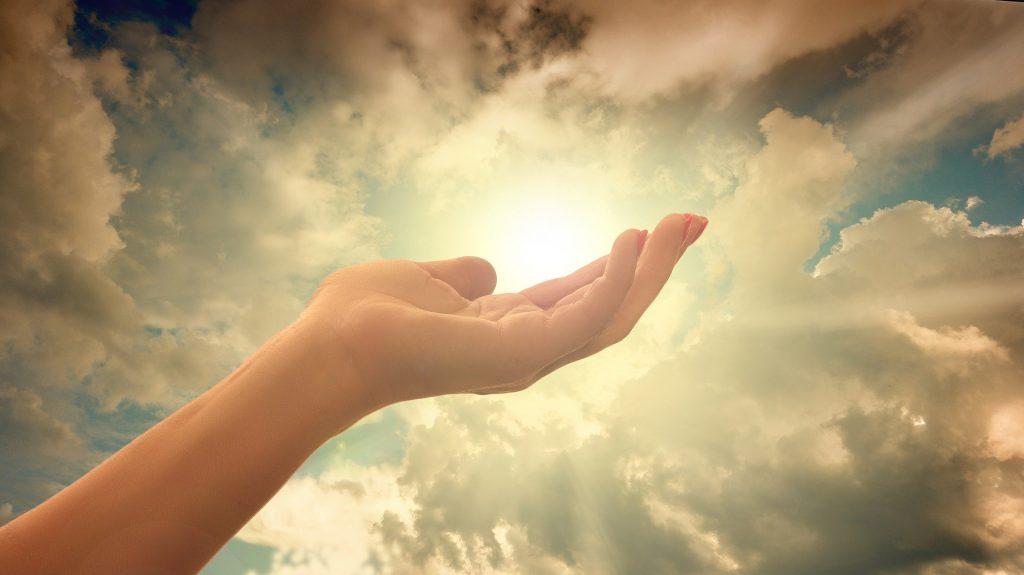 Mão esticada em direção ao sol no céu, que está cercado por nuvens.