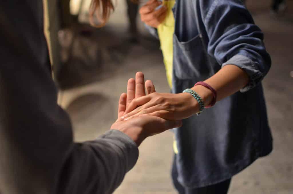 Pessoas segurando mão de outra pessoa para ajudar