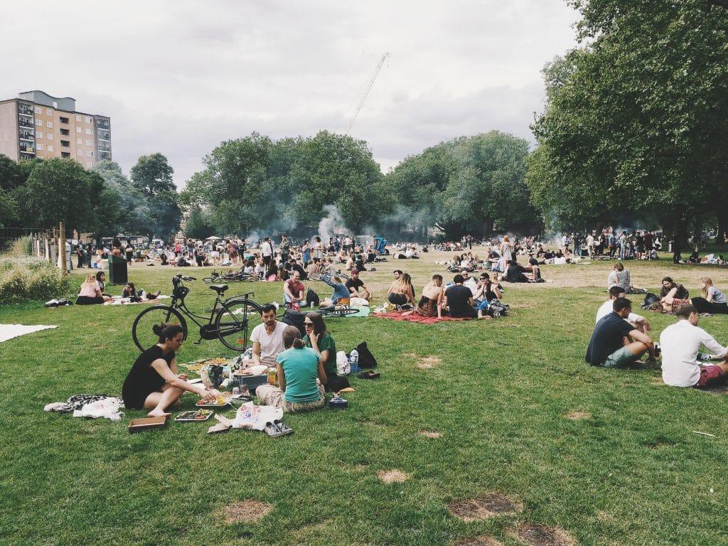 Grupo de pessoasl em um parque sentados conversando, sindo