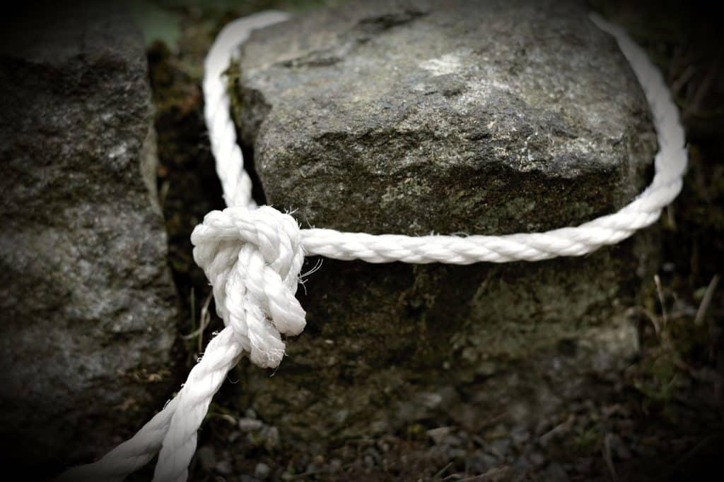 Imagem de uma corda de nylon branca com um nó.