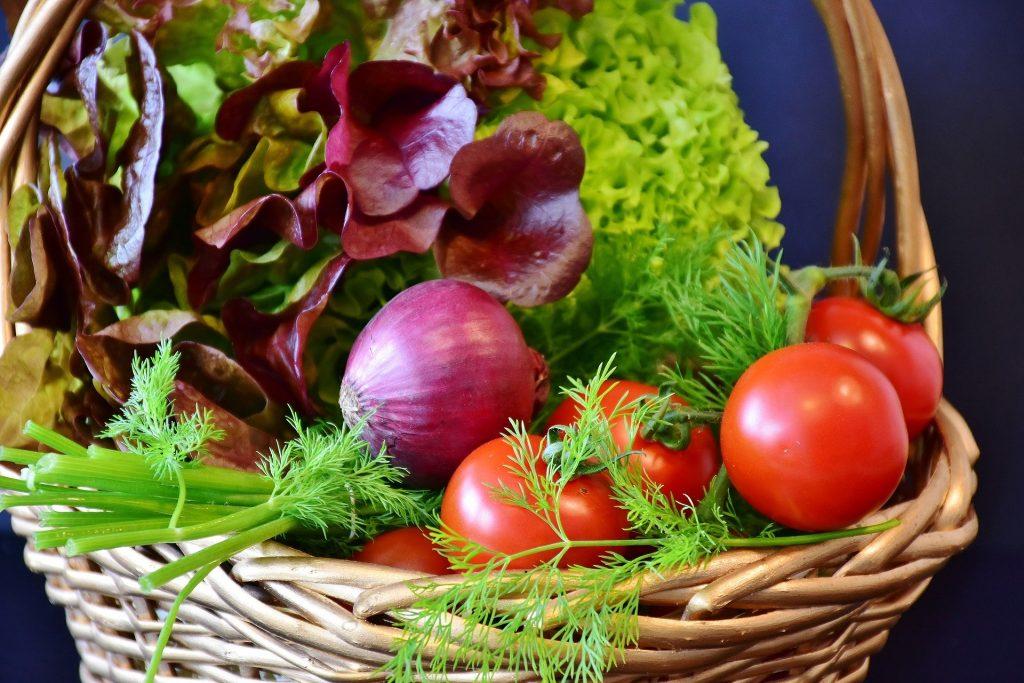 Imagem de um cesta de vime grande repleta de alimentos naturais e fotoprotetores como: verguras, legumes e ervas diversas.