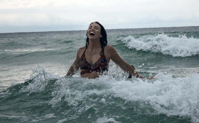 Mulher de biquini no mar, com ondas quebrando atrás dela. Ela está de braços abertos e sorrindo com a boca aberta.