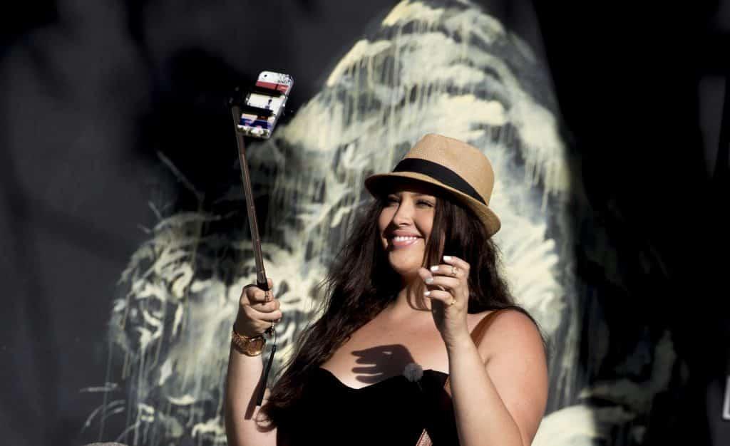 Imagem de uma mulher de cabelos longos e chapeu panamá fazendo um selfie para as redes sociais.