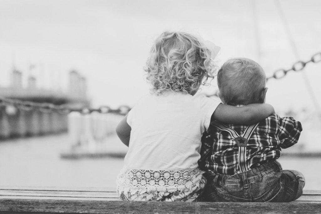 Imagem em preto e branco de duas crianças sentadas. A criança maior abraça a criança menor. Luto imagem.