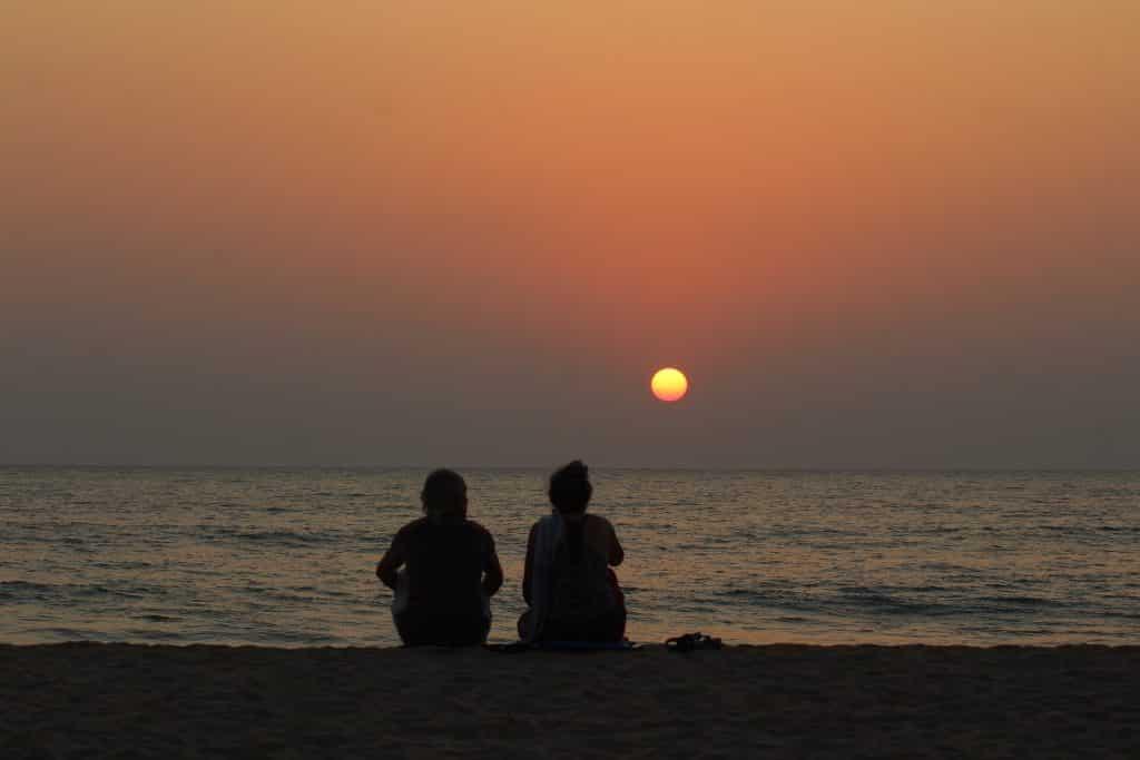 Imagem da silhueta de um casal homem e mulher sentandos na areia de uma praia assintindo o por do sol.