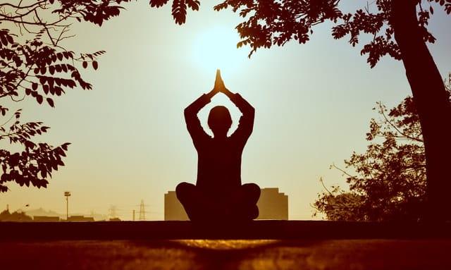 Silhueta de pessoa meditando, sentada e com os braços para cima, unindo as palmas das mãos.