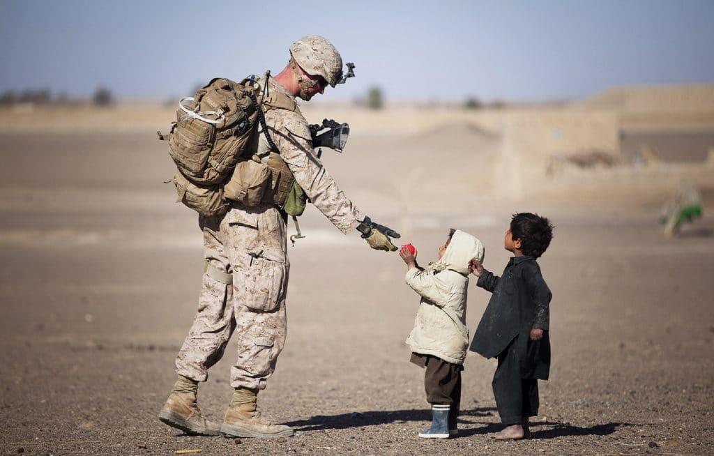 Homem militar em serviço recebe alimento de duas crianças.