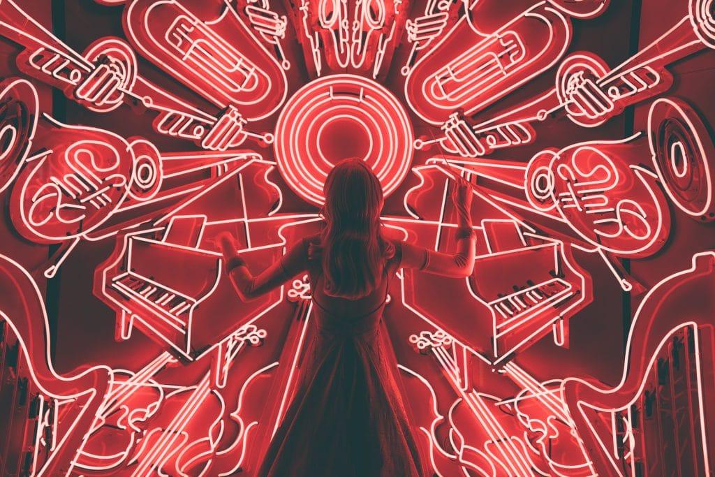 Mulher de costas em painel de led com desenhos de instrumentos musicais