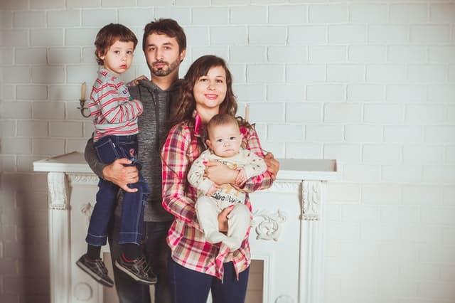 Família com pai, mãe e filhos nos colos