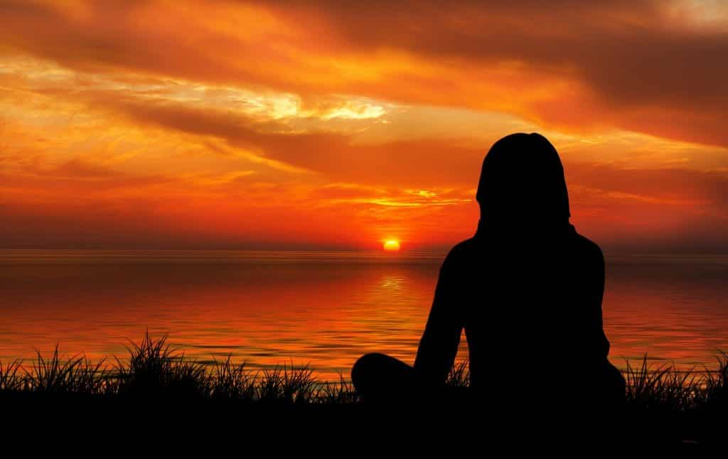 Imagem de uma mulher meditando em frente ao mar e apreciando um lindo por do sol.